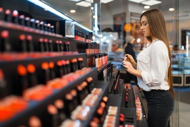Frau hält nagellack am regal im kosmetikladen. käufer an der vitrine im luxus-beauty-shop-salon, kundin im modemarkt