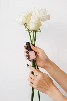 Frau hält nagellack und blumen, schönheitssalon