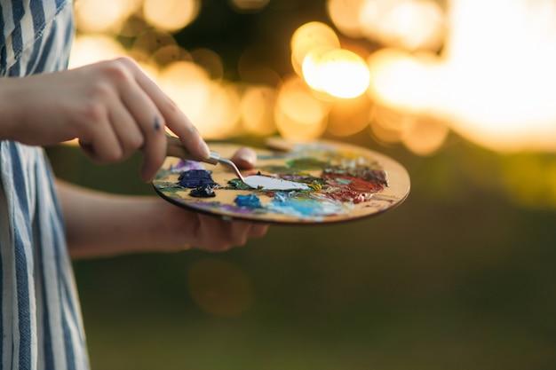 Frau hält palette mit farben und spatel