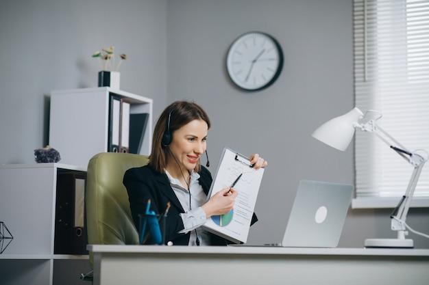 Frau hält papier finanzbericht gespräch bei webcam machen videoanruf im büro, business coach blick auf die kamera sprechen show statistik erklären marketing-strategie für kunden, online-training