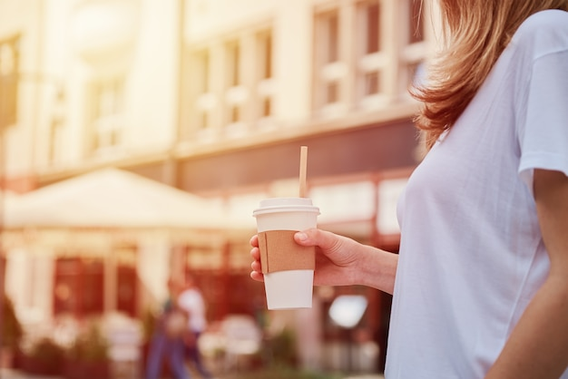 Frau hält papierkaffeetasse an der stadtstraße