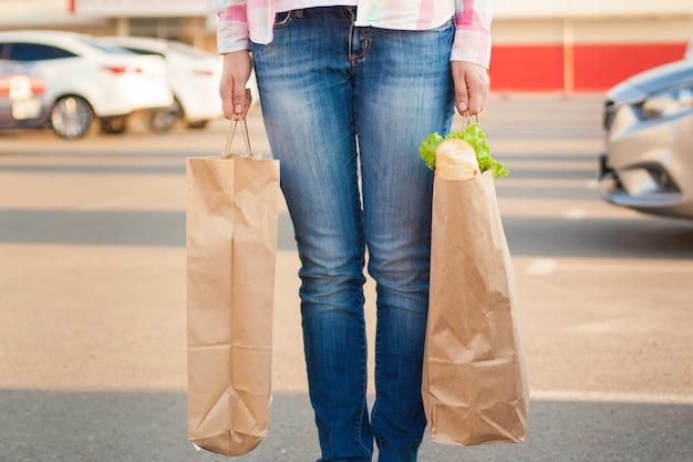 Frau hält papiertüten mit lebensmitteln in der nähe eines supermarktes.