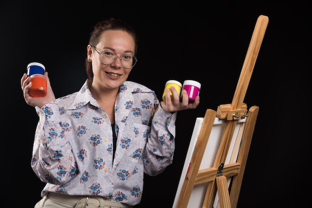 Frau hält pinsel und malt auf schwarzem hintergrund
