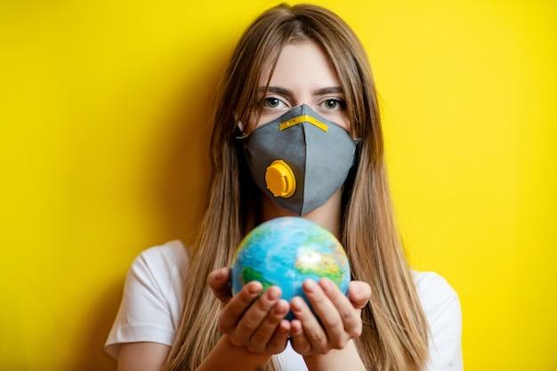 Frau hält planetenerdekugel, die maske trägt