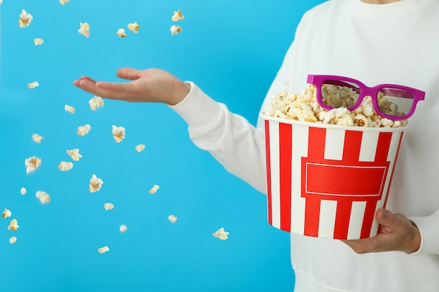 Frau hält popcorn mit 3d-brille auf blauem hintergrund mit fliegendem popcorn.