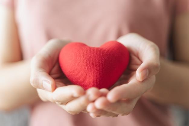 Frau hält rotes herz liebe krankenversicherung spende glücklich wohltätigkeitsorganisation freiwilliger tag der psychischen gesundheit