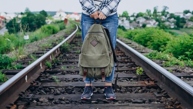 Frau hält rucksack und steht auf eisenbahnschiene.