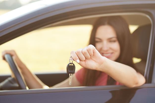 Frau hält schlüssel, während sie im luxusauto sitzt, froh, teures geschenk von verwandten zu erhalten, konzentriert sich auf schlüssel