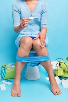 Frau hält schwangerschaftstest mit positivem ergebnis und erfährt von der zukünftigen mutterschaft in freizeitkleidung posiert auf der toilettenschüssel aus porzellan auf der toilette