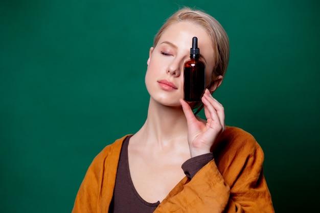 Frau hält schwarze flasche auf grüner szene