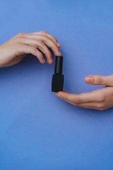 Frau hält schwarze wimperntusche in der hand