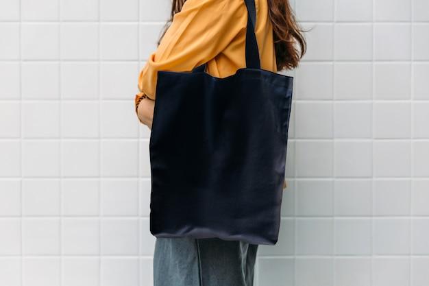 Frau hält schwarzes taschensegeltuchgewebe