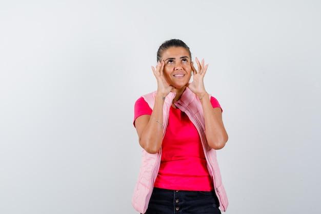 Frau hält sich an den händen in t-shirt, weste und sieht hoffnungsvoll aus