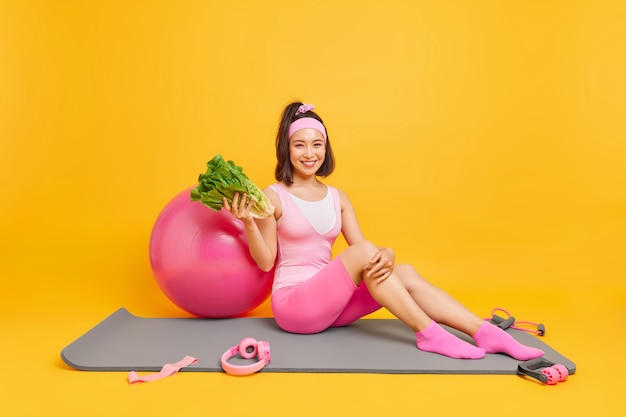 Frau hält sich an gesunde ernährung hält grünes frisches gemüse sitzt auf mattenposen um sportgeräte