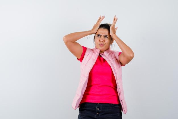 Frau hält sich die hände am kopf in t-shirt, weste und sieht vergesslich aus
