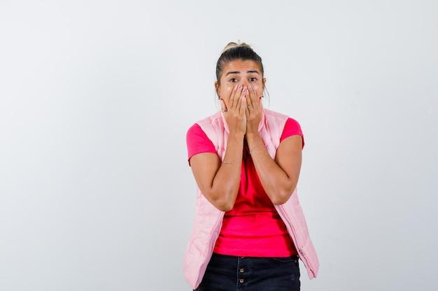 Frau hält sich in t-shirt und weste die hände am mund und sieht verängstigt aus