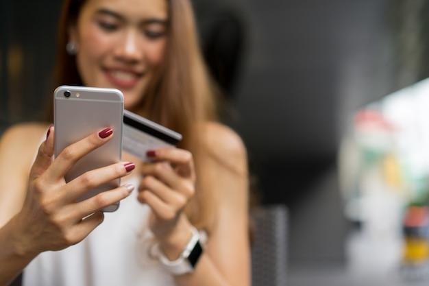 Frau hält smartphone mit kreditkarte für online-shopping