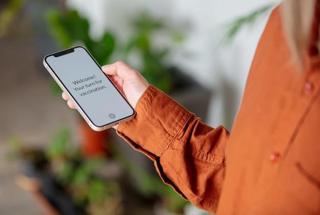 Frau hält smartphone mit text - willkommen, sie sind an der reihe für die impfung