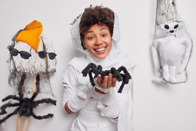 Frau hält spinne macht zaubertrick lächelt glücklich entwickelt fantasie eingehüllt in weißen stoff posen drinnen. fantasie und kreativität. es ist zu süß zum gruseln