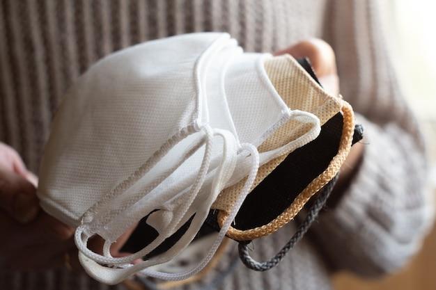 Frau hält stapel hausgemachter wiederverwendbarer antiviraler schutzmasken