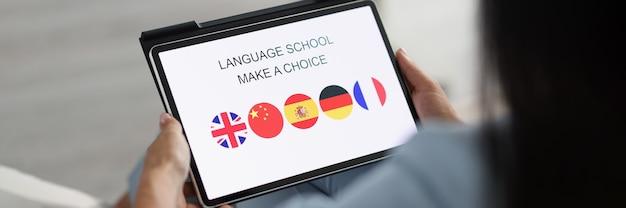 Frau hält tablet und wählt eine fremdsprache zum lernen