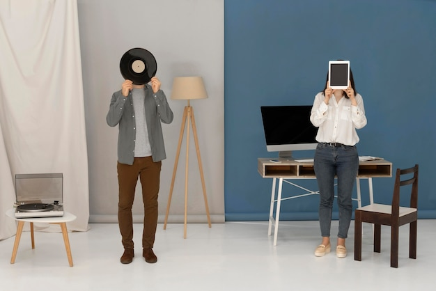Frau hält tablette und mann hält vinyl