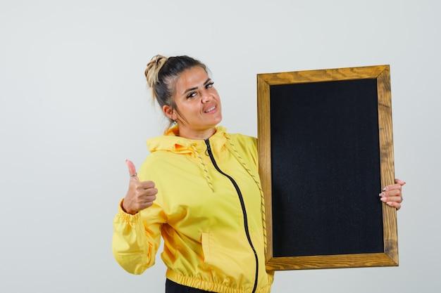 Frau hält tafel, zeigt daumen oben im sportanzug und schaut fröhlich. vorderansicht.