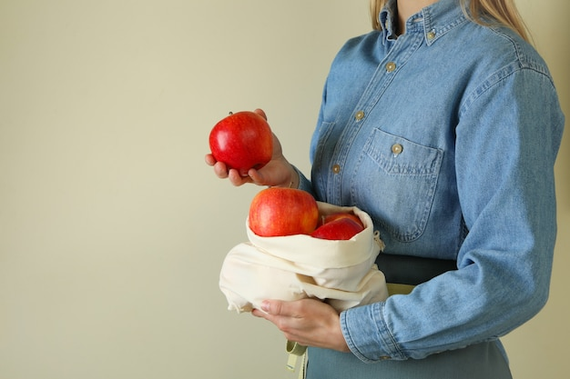 Frau hält tasche mit reifen roten äpfeln