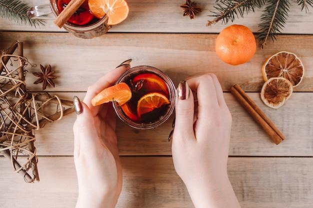 Frau hält tasse heißen glühwein in ihren händen. winterwärmendes getränk für die feiertage.