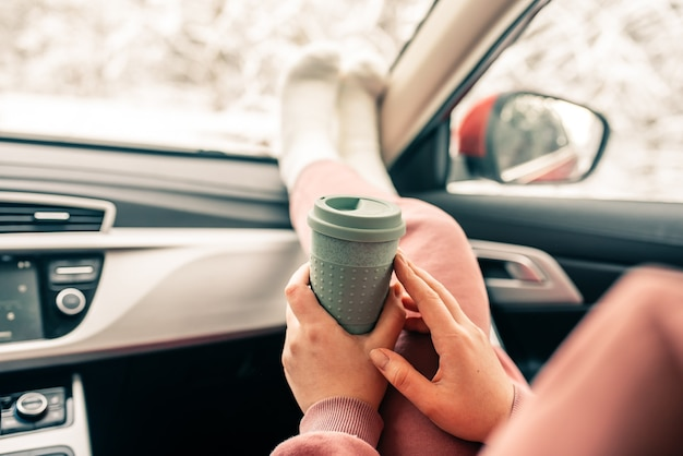 Frau hält tasse kaffee im auto. reiselebensstil. beine am armaturenbrett.