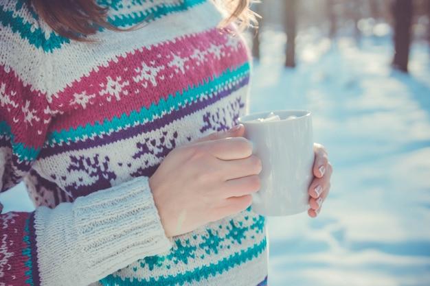 Frau hält tasse kaffee mit eibisch im winterwald
