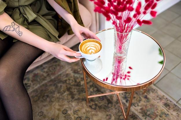Frau hält tasse leckeren cappuccino und genießt zeit im restaurant, ausgefallene atmosphäre, kaffeeliebhaber.