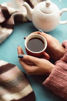 Frau hält tasse warmen tee an der blauen wand. freuden des herbstes. krankheitsprävention