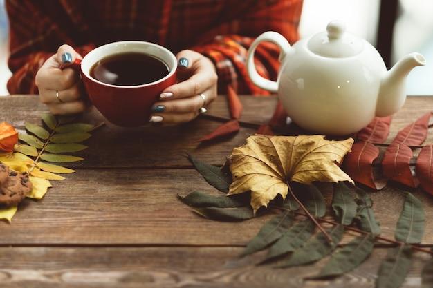 Frau hält tasse warmen tee an der herbstlichen wand. freuden des herbstes. krankheitsprävention
