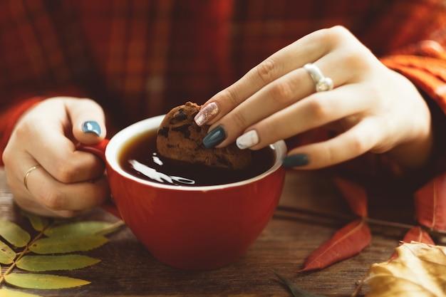 Frau hält tasse warmen tee und keks an der herbstlichen wand. freuden des herbstes. krankheitsprävention