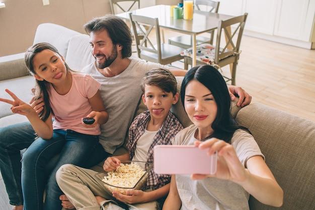 Frau hält telefon in händen und macht selfie ihrer familie