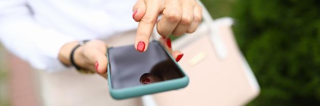 Frau hält telefon in ihrer hand und zeigt finger auf smartphone. entwicklung neuer angebote für das telefonkonzept
