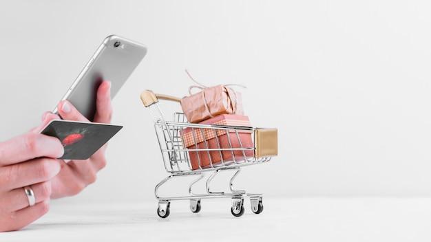Frau hält telefon und kreditkarte