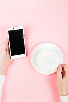 Frau hält telefon und trinkt kaffee auf rosa raum. draufsicht, kopierraum