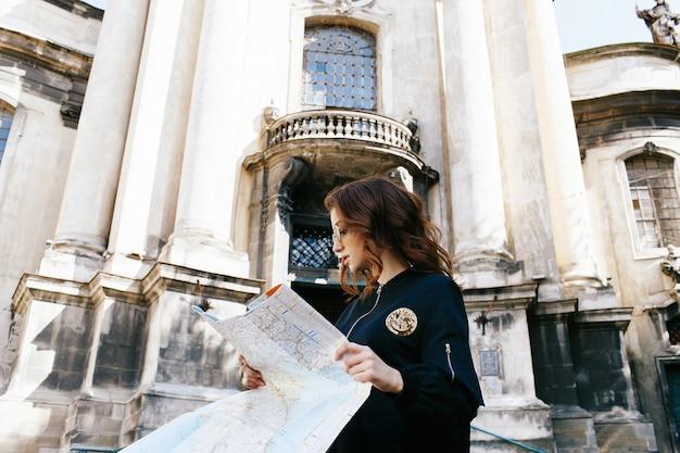 Frau hält touristische karte in ihrem arm, der vor alter kathedrale steht