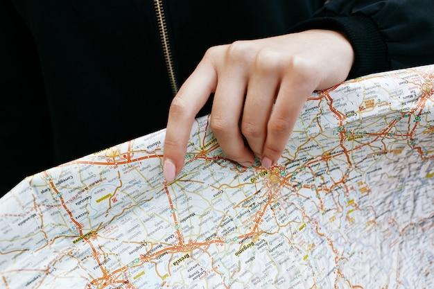 Frau hält touristische karte in ihrem arm