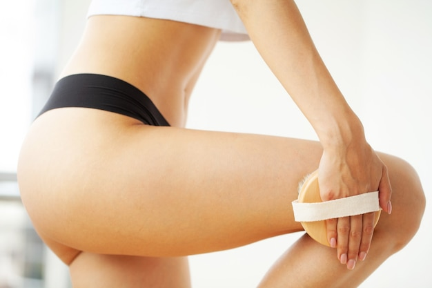 Frau hält trockene bürste auf ihrem bein
