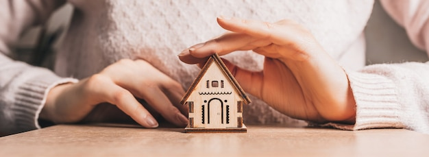 Frau hält und schützt ein holzhaus mit ihren händen mit der sonne auf einem hellrosa hintergrund. süßes zuhause
