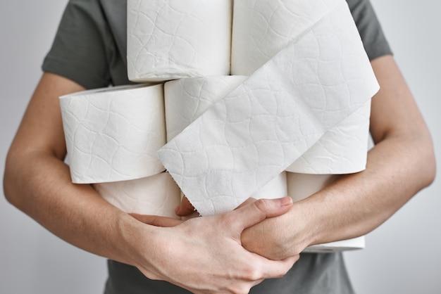 Frau hält viele rollen toilettenpapier. panikkonzept, bevorratung von toilettenpapier für die quarantäne zu hause