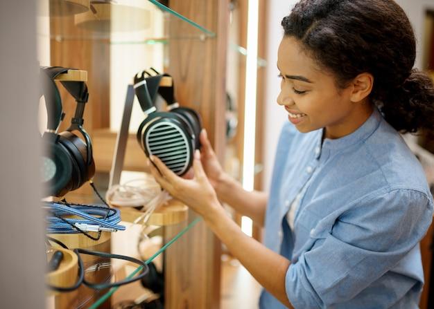 Frau hält vintage-kopfhörer im audiokomponentengeschäft. weibliche person im musikgeschäft, schaufenster mit kopfhörern, käufer im multimedia-geschäft