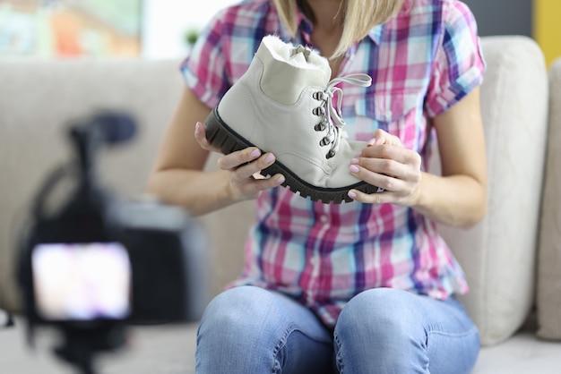 Frau hält warmen stiefel in den händen vor der kamera