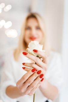 Frau hält weiße rose, vorderansicht, fokus auf maniküre und blumenschönheitssalon.