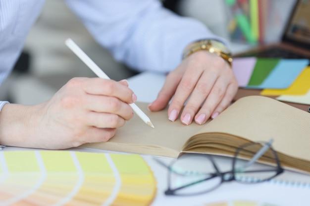 Frau hält weißen bleistift und notizbuch auf dem desktop in der hand und arbeitet als designer