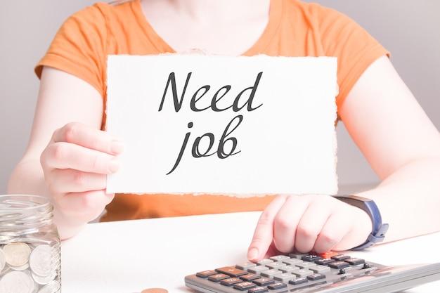 Frau hält weißen karton mit inschrift brauchen job