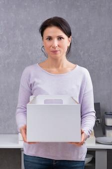 Frau hält weißen karton. verpackung für kuchen und gebäck.